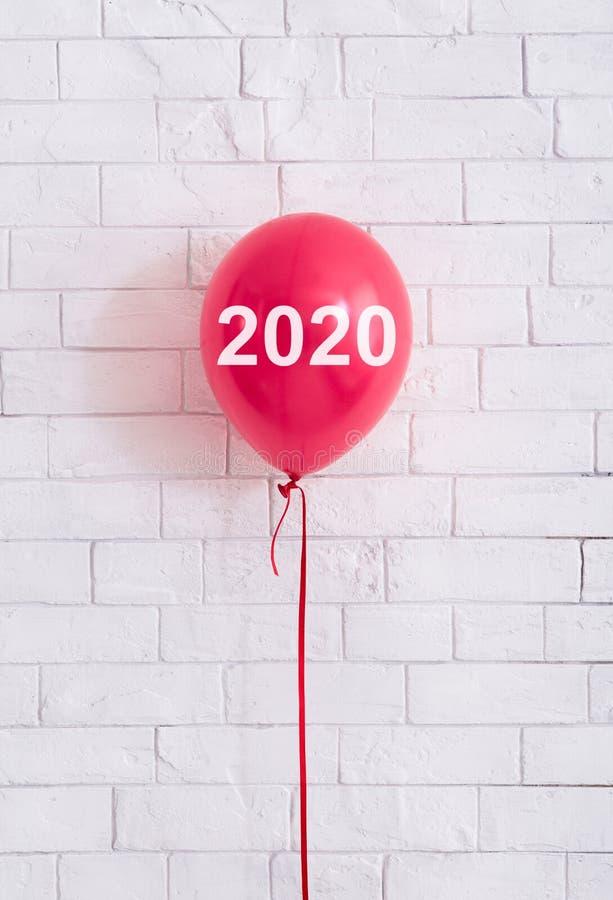 Röd ballong med begreppet 2020 framme av wal vita tegelstenar royaltyfri bild
