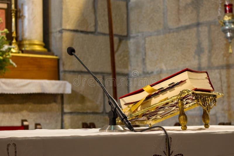 Röd bibel på altaretabellen med mikrofonen Tro- och religionbegrepp Predika bakgrund kyrklig interior Herres tabellbegrepp royaltyfria bilder