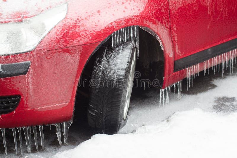Röd bil med djupfrysta gummihjul som står i vinter royaltyfri bild