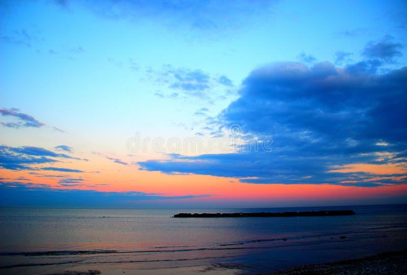 Röd-blått himmel möter havet royaltyfria foton