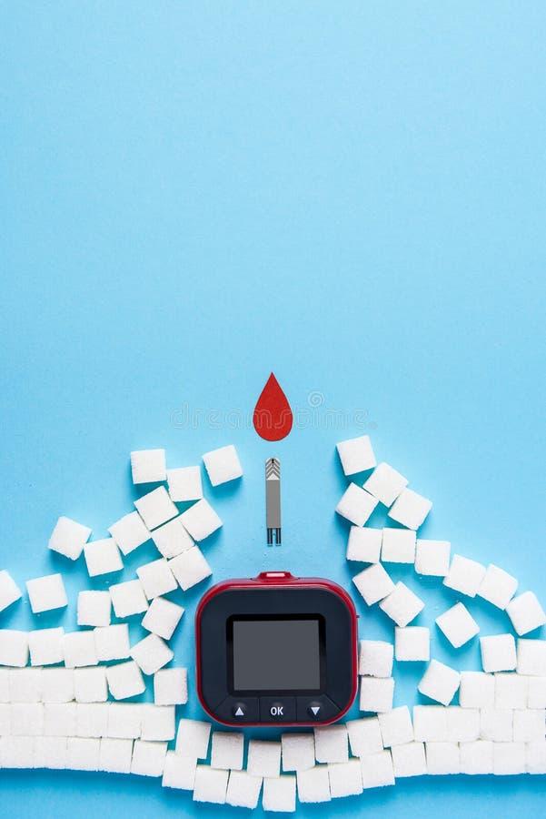 Röd bloddroppe och vägg som göras av sockerkuber som fördärvas av remsor för prov för blodglukos och glukosmetern på blå bakgrund royaltyfri fotografi