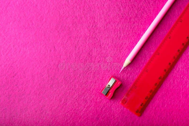 Röd blyertspenna med vässaren och linjal på röd bakgrund brevpapper royaltyfria foton