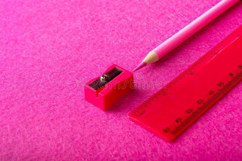 Röd blyertspenna med vässaren och linjal på röd bakgrund brevpapper royaltyfri fotografi