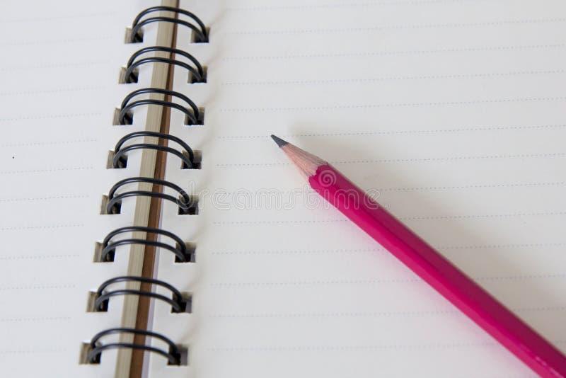Röd blyertspenna på anteckningsboksidan arkivbild