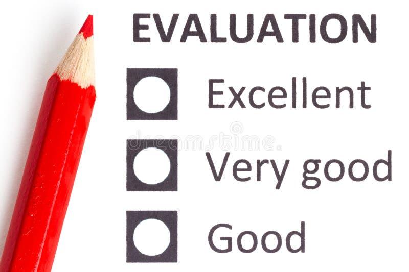 Röd blyertspenna på en evaluationform arkivfoton