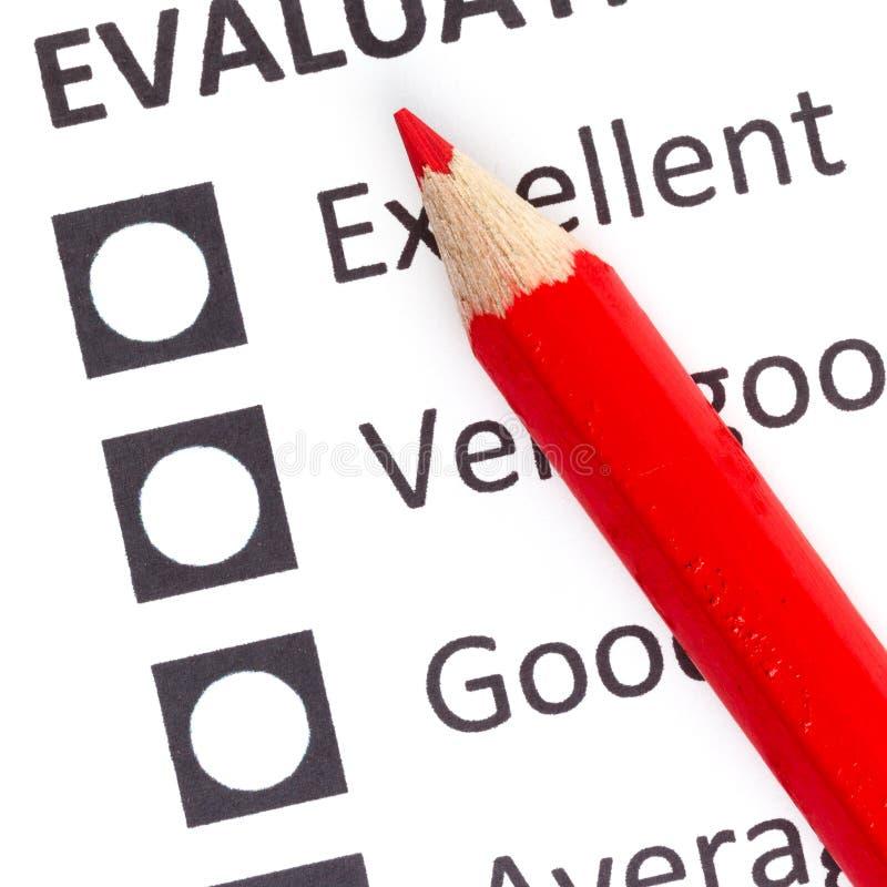 Röd blyertspenna på en evaluationform arkivbild