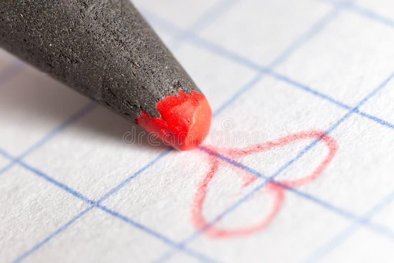 Röd blyertspenna på papper Makro royaltyfri foto