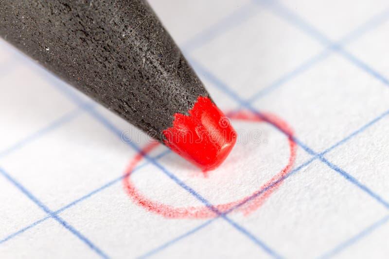 Röd blyertspenna på papper Makro arkivbild