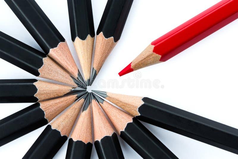Röd blyertspenna som står ut från cirkeln av svarta blyertspennor arkivfoto