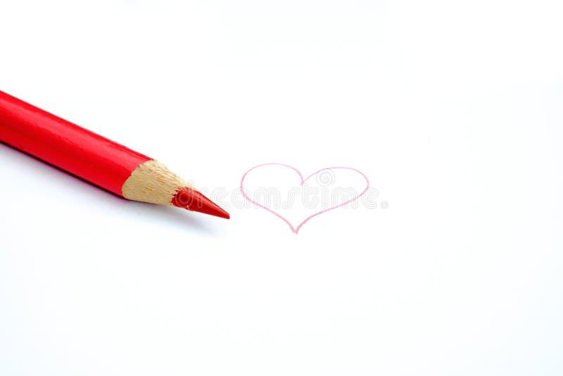 Röd blyertspennafärgpenna och en hjärta royaltyfria bilder
