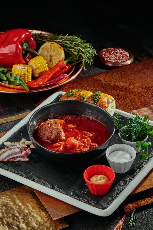 Röd borsch gjorde av beetrot, grönsaker och kött med gräddfil i en svart platta på en kopparbakgrund royaltyfri foto