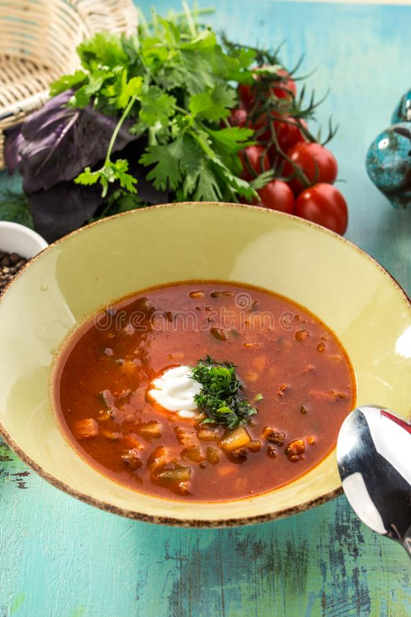 Röd borshch för rödbetasoppa med nötkött och gräddfil på den blåa trätabellen royaltyfri foto