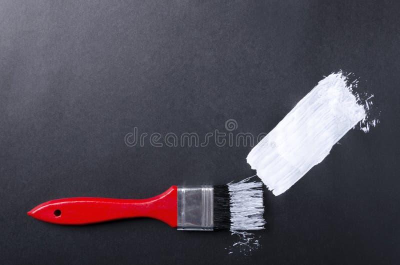 Röd borste, vit målarfärgslaglängd på den svarta bakgrunden T?m utrymme f?r design royaltyfri bild