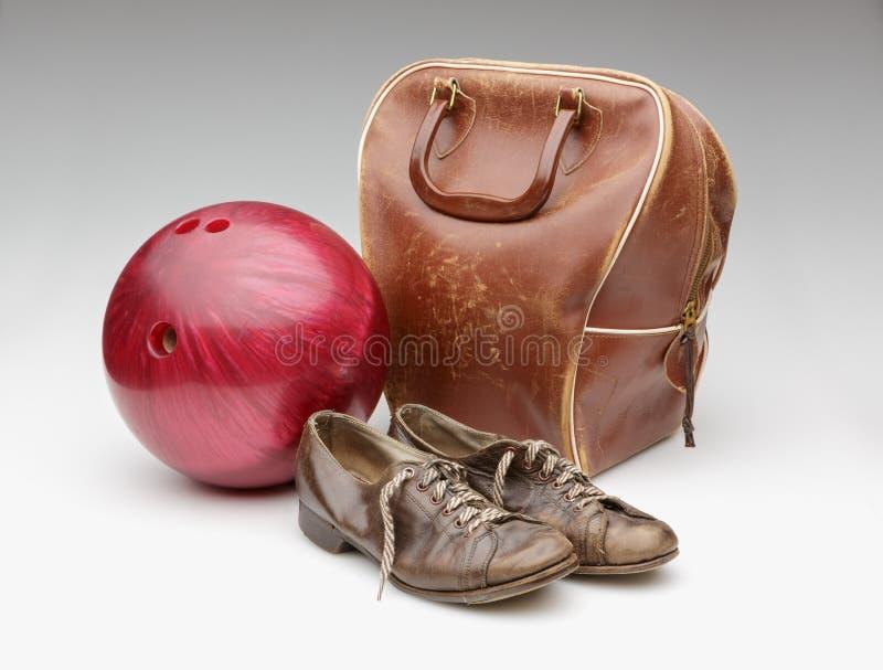 Röd bowlingklot för tappning, bekymrad läderpåse och bruntskor arkivfoto