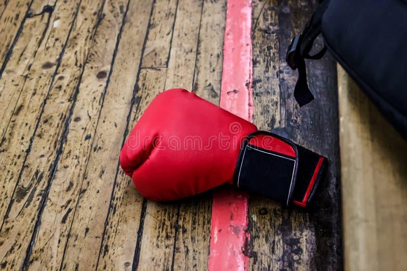 Röd boxninghandske på idrottshallgolvet med träbeläggning Närliggande är en svart ryggsäck Sportar och utbildning, brottning och  arkivfoto