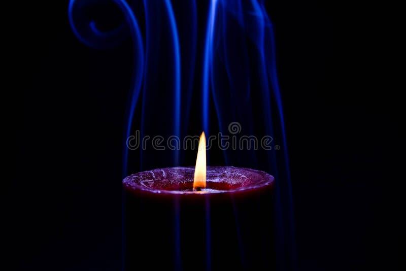 Röd bränningstearinljus med blått färgad rök fotografering för bildbyråer