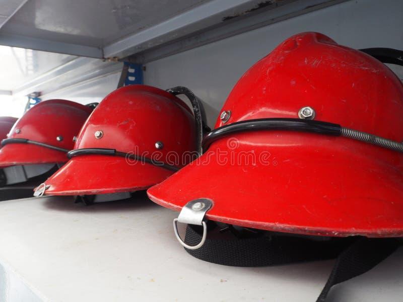 Röd brandmanhjälm som är förberedd på hylla royaltyfri foto