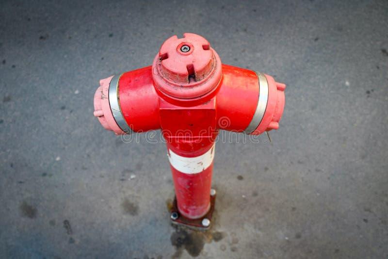 Röd brandsläckare mot grå sidopromenad arkivfoto