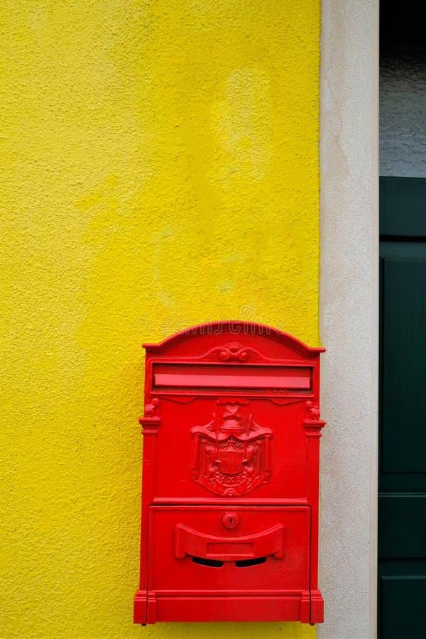 Röd brevlåda som hänger på en gul vägg arkivfoton