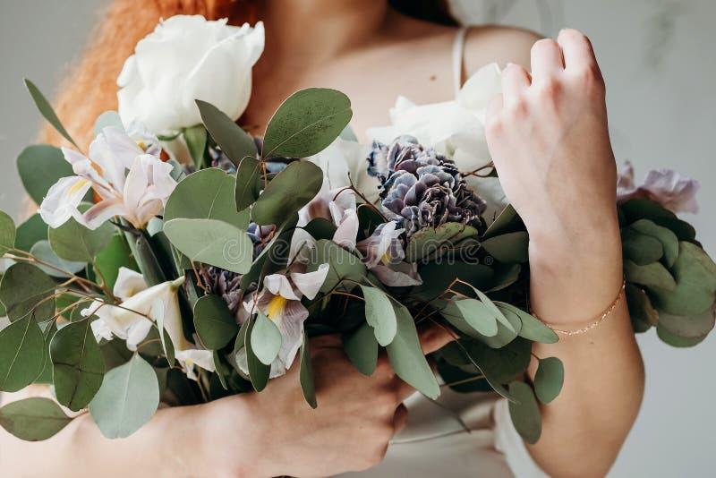 Röd brud i en bröllopsklänning i elfenben Flickan har en lush-bukett av vita rosor med gröna blad, fotografi i rummet, ligg royaltyfri fotografi