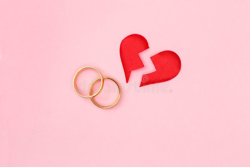 Röd bruten hjärta delar itu stycken med par av guldbröllopcirklar på rosa bakgrund royaltyfria foton