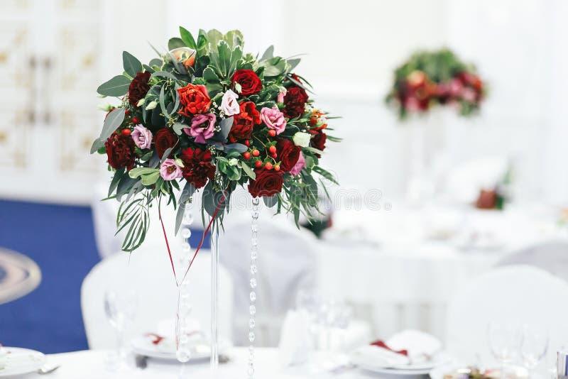 Röd bukett av grönska och rosor på den höga vasen på weddinen arkivfoton