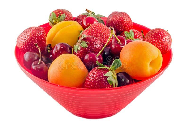 Röd bunke, vas som fylls med frukter arkivbild