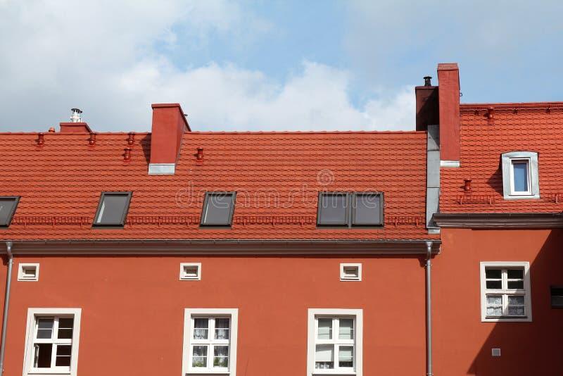 Röd byggnad med tegelplattataket mot blå himmel royaltyfri fotografi