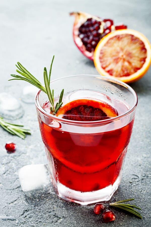 Röd coctail med blodapelsinen och granatäpplet Uppfriskande sommardrink Ferieaperitif för julparti arkivfoto