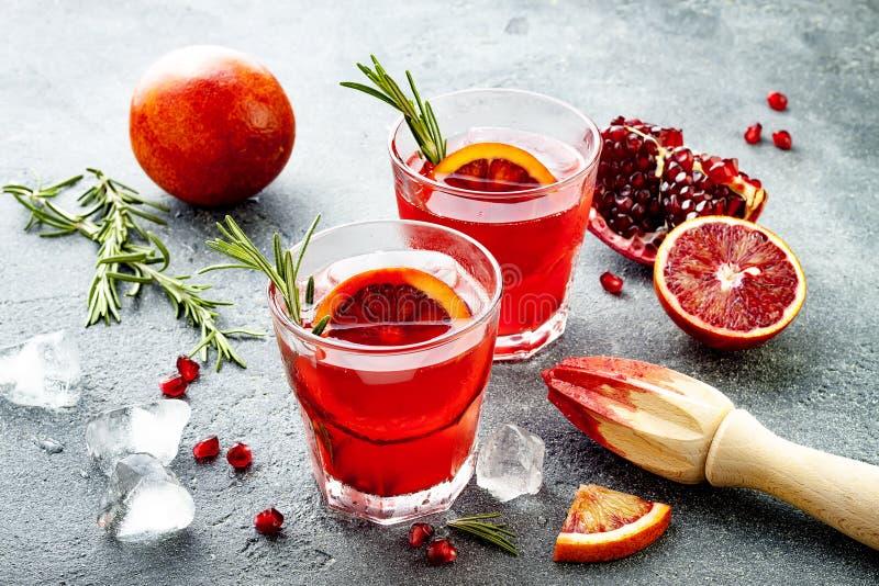 Röd coctail med blodapelsinen och granatäpplet Uppfriskande sommardrink Ferieaperitif för julparti royaltyfri bild