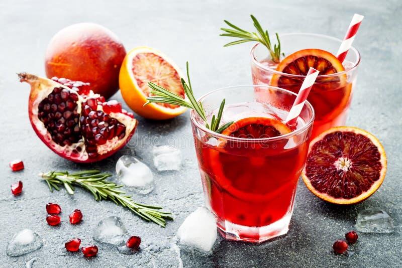 Röd coctail med blodapelsinen och granatäpplet Uppfriskande sommardrink Ferieaperitif för julparti arkivbilder