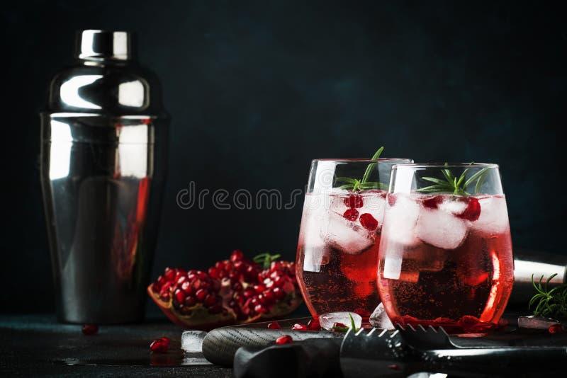 Röd coctail med kall vodka- och granatäpplefruktsaft, iskuber och rosmarin, stånghjälpmedel, blå svart stångräknarebakgrund, kopi royaltyfri fotografi