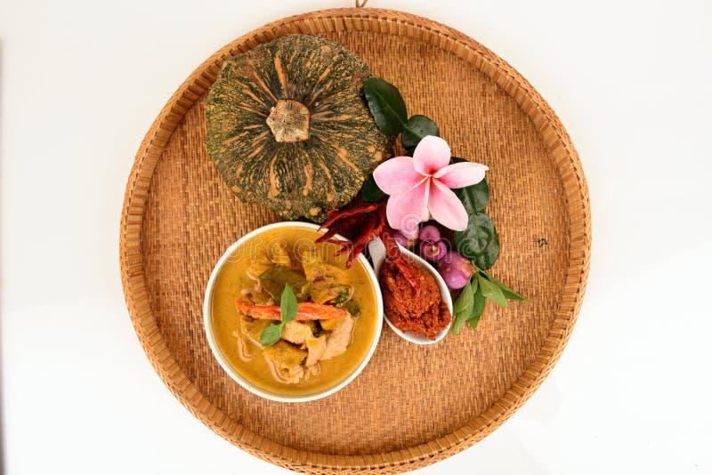 Röd curry med griskött och pumpa och ingrediens: Pumpa grisköttskiva, chilideg, Basilika thailändsk basilika, citronblad, Kaffirl fotografering för bildbyråer
