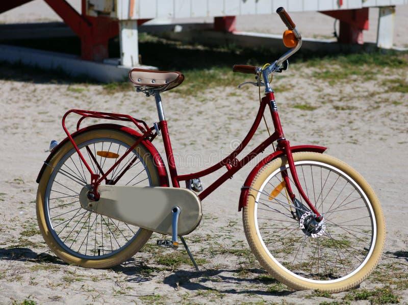 Röd cykel för gammal tappningstil i stranden arkivfoton