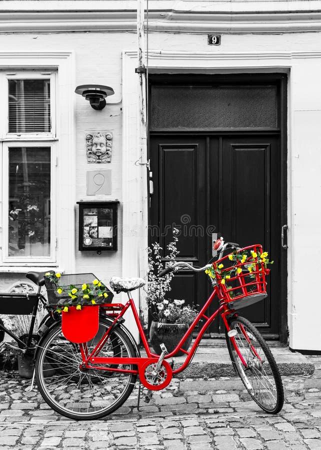 Röd cykel för Retro tappning på kullerstengatan i den gamla staden royaltyfri foto