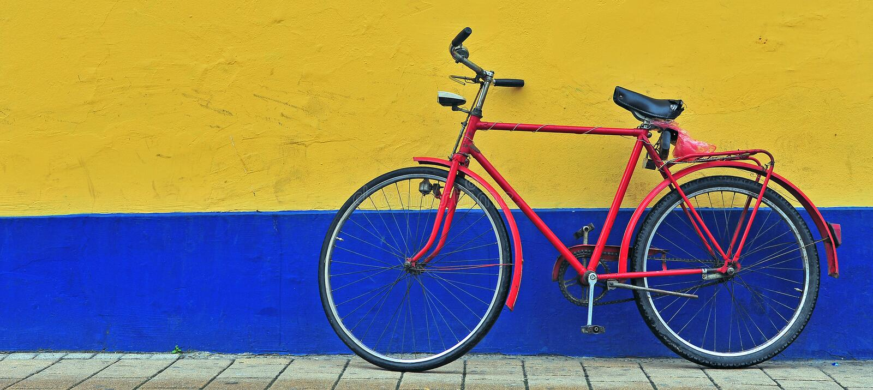 Röd cykel framme av guling- och blåttväggen arkivbilder