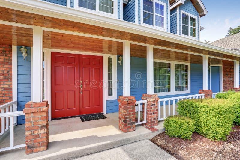 Röd dörr för främre tillträde med den konkreta golvfarstubron royaltyfri fotografi