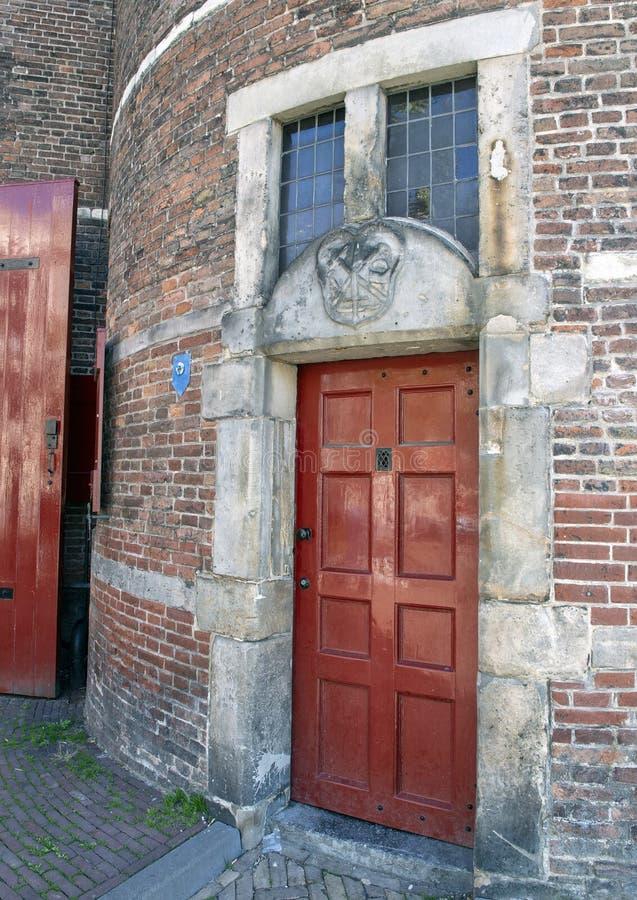 Röd dörr och Gable Stone för hovslagarens skrå, Waag hus, Amsterdam, Nederländerna royaltyfri foto