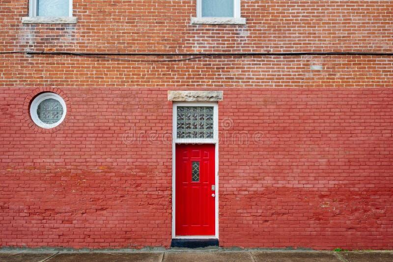 Röd dörr på byggnad för röd tegelsten royaltyfria bilder