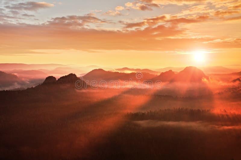 Röd dimmig gryning Dimmig höstmorgon i härliga kullar Maxima av kullar klibbar ut från rika färgrika moln arkivbild