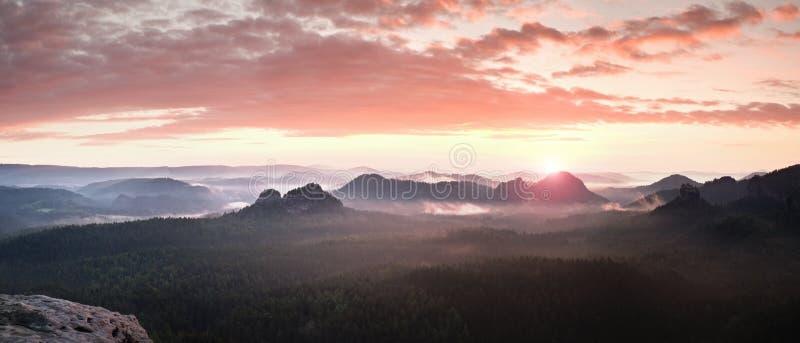 Röd dimmig landskappanorama i berg Fantastisk drömlik soluppgång på steniga berg Dimmig dimmig dal under royaltyfria foton