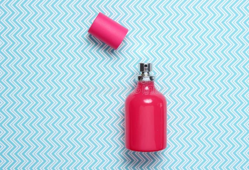 Röd doftflaska på en idérik blå bakgrund, minimalism, bästa sikt arkivfoto