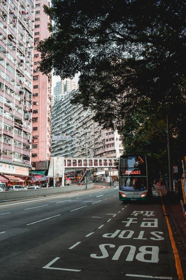 Röd dubbel däckare på en hållplats i bostads- del av Hong Kong fotografering för bildbyråer