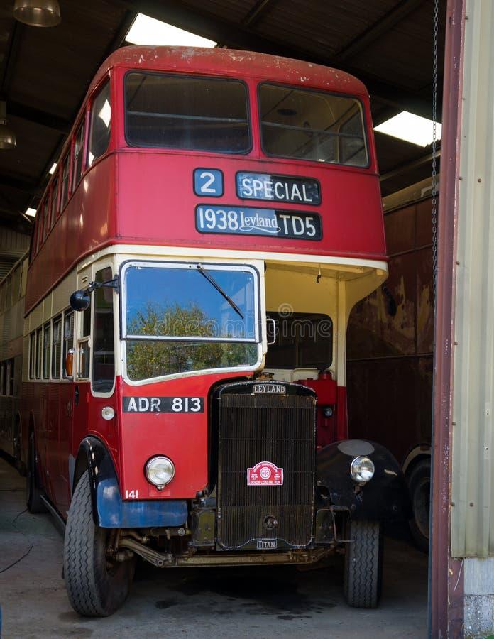 Röd dubbeldäckarebuss för tappning i garaget som är klart för den årliga Devon kust- körningen, Winkleigh, Förenade kungariket, A arkivbild