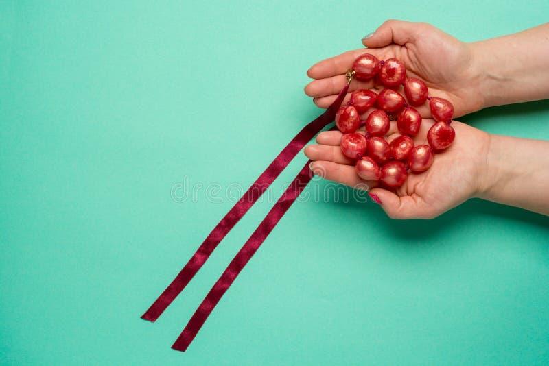 Röd elegant halsband i kvinnliga händer på grön bakgrund fotografering för bildbyråer