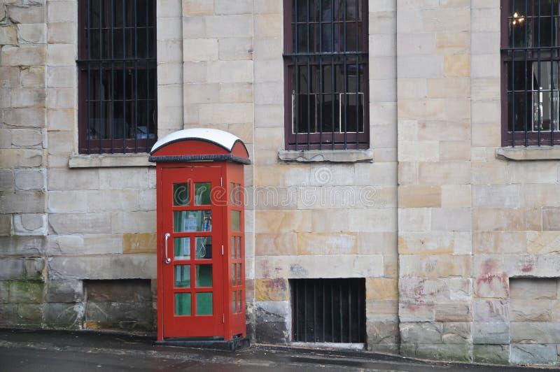 Röd engelsk traditionell ask för offentlig telefon på en gata royaltyfri foto