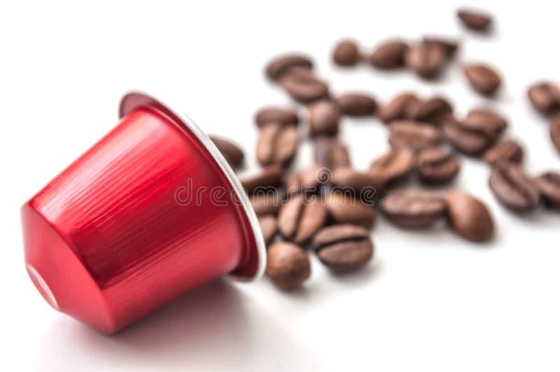röd espressokaffekapsel med kaffebönor på whit arkivfoto