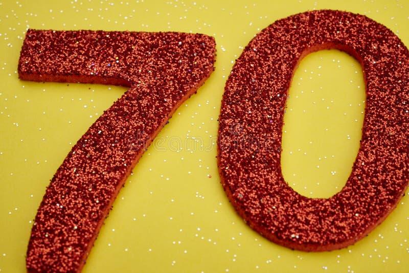 Röd färg för nummer sjuttio över en gul bakgrund årsdagen vektor illustrationer