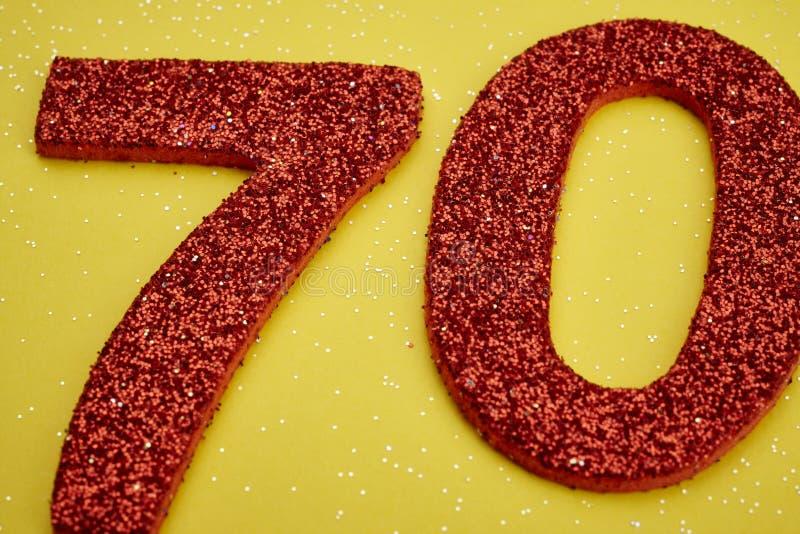 Röd färg för nummer sjuttio över en gul bakgrund årsdagen stock illustrationer