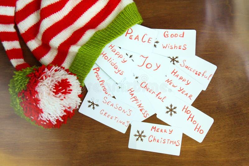Röd färgrik jul, vit och den gräsplan stack Santa Claus hjälpredahatten, naturlig ull, handgjort stuckit, med jul önskar på p royaltyfri bild